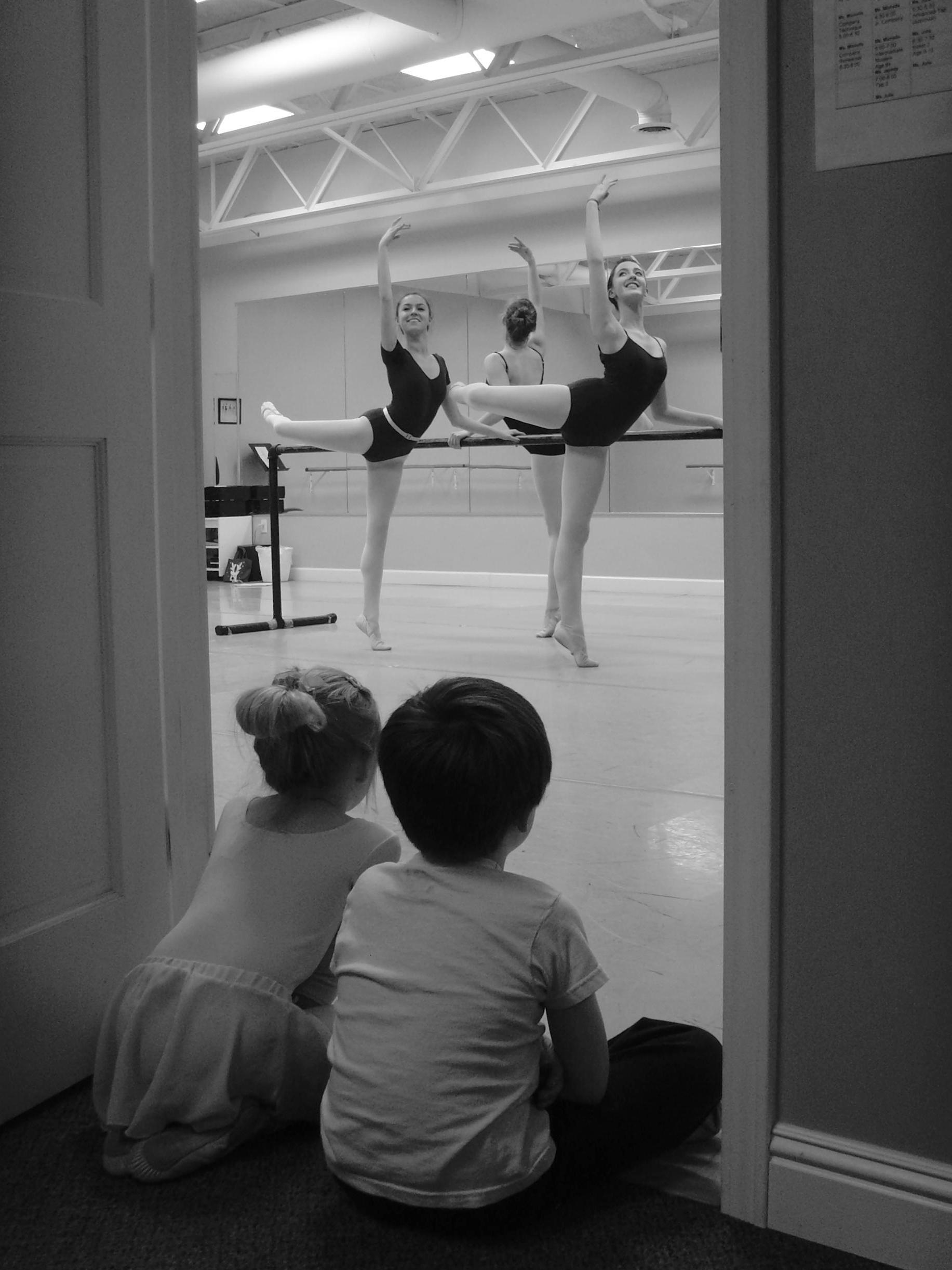 Photo of two dancers being watched by young students at RCYBE, we grow dancers one step at a time